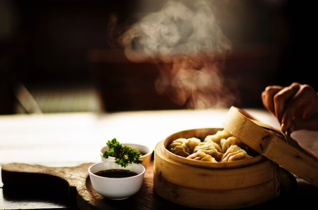 Fresh dumplings in steamer with soy and chilli sauce