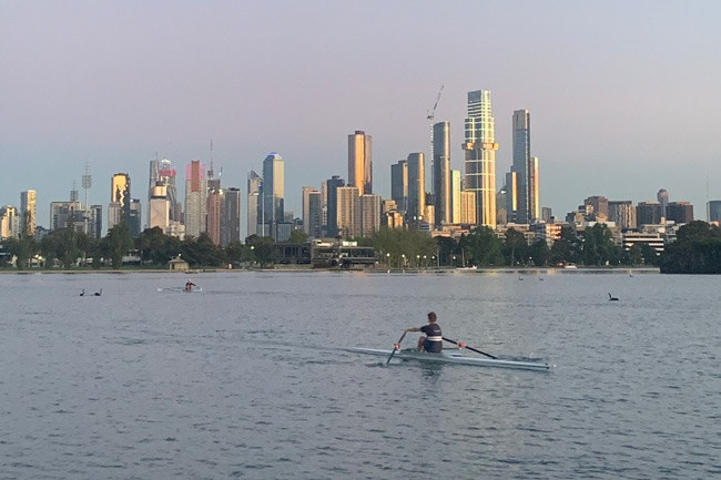 Men rowing on albert park lake, with Melbourne CBD in the background