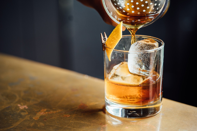 old fashioned cocktail being poured