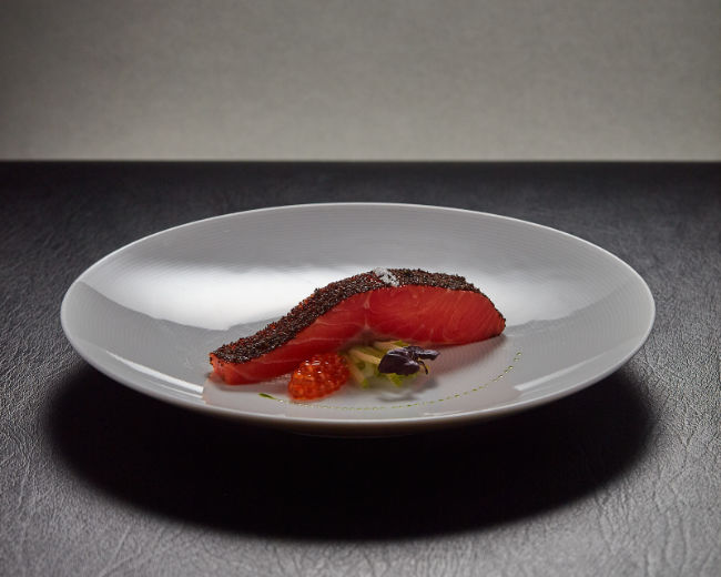 salmon coated in roe arranged beautifully on a plate