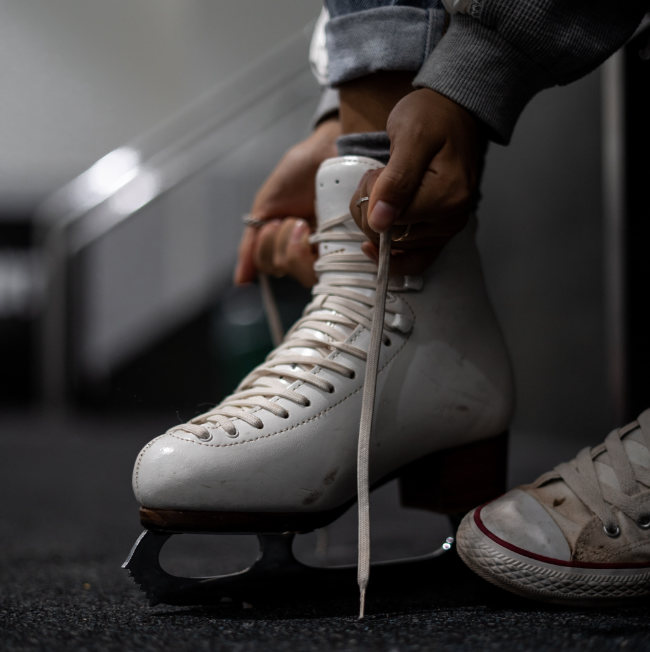 a skater strapping on their ice skates and getting ready to go ice skating