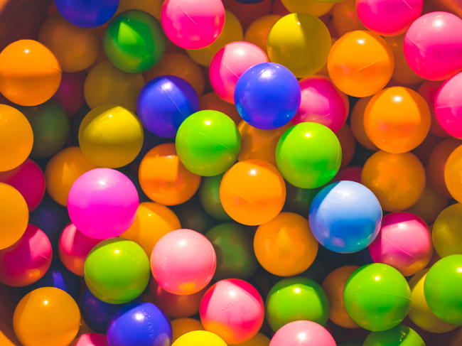 a colourful assortment of balls in a play pit