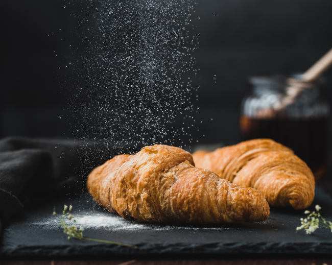 a vegan crossiant being dusted with icing sugar