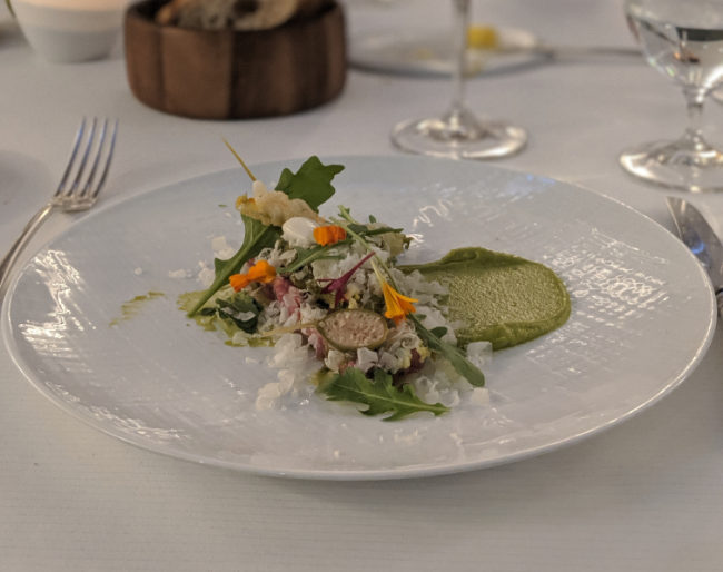 Fancy vegan food arranged on a plate with vegetables, edible flowers and pea puree