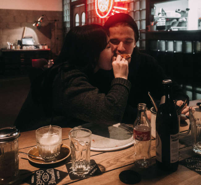 a happy couple eating vegan food in a pub