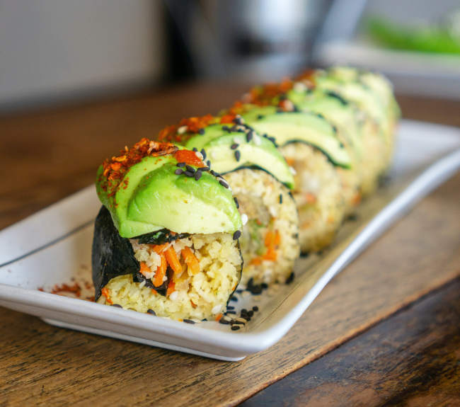 Vegan sushi topped with sliced avocado neatly arranged on a plate and looking good