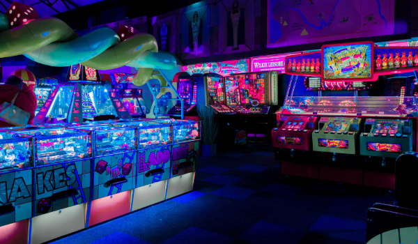 the inside of an arcade with neon lights everywhere