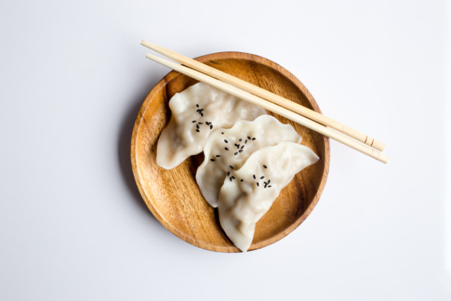 vegan dumplings sprinkled with sesame seeds and in a bowl with chopsticks