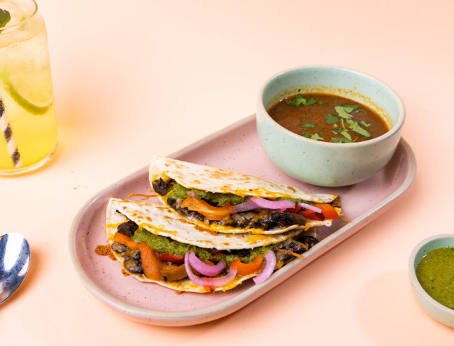 a plate of vegan tacos filled with vegetables