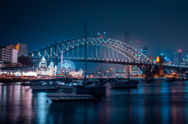 yachts sailing on the sydney harbour at night and it's beautiful