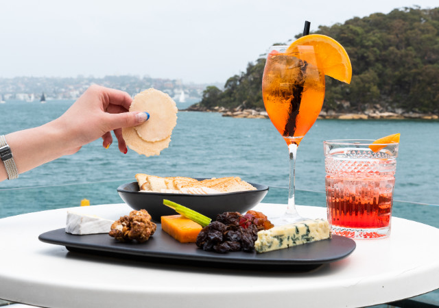 a delicious cheese platter with the water in the background