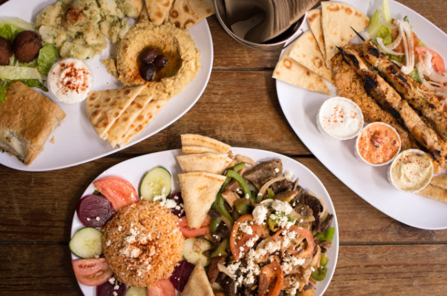 3 plates of pita bread, dips and fresh vegetables