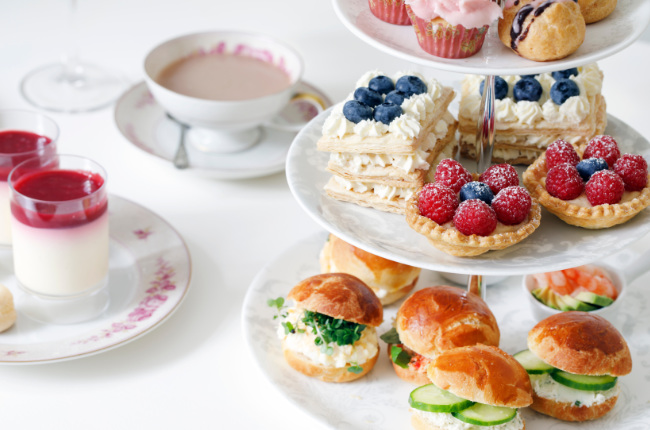 a selection of tarts, creams and sandwiches