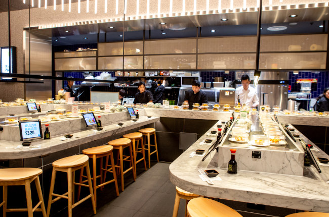 the inside of a sushi train restaurant with rows of tables